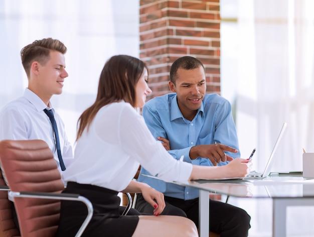 Сотрудники разговаривают с клиентом, сидящим за столом