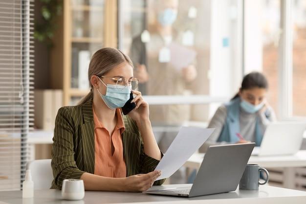 オフィスでフェイスマスクを着用している従業員