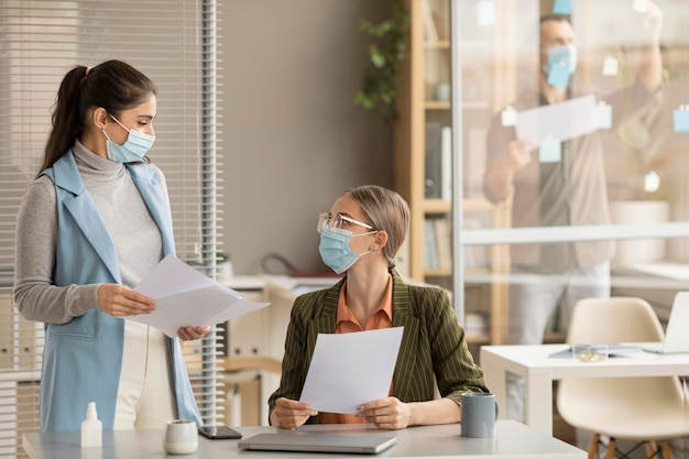 Dipendenti che indossano maschere facciali in ufficio