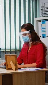 마스크와 바이저를 착용한 직원들은 사회적 거리를 존중하는 새로운 일반 사무실에 앉아 있습니다. 현대 직장에서 일하는 동료들은 플렉시글라스를 사용하여 코비드 바이러스에 대한 보호 규칙을 준수합니다.
