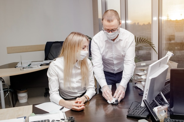 Работники в защитной маске и дезинфицирующие рабочие места с дезинфицирующими средствами