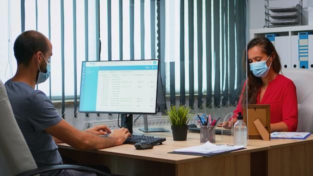 Dipendenti con maschere facciali che puliscono le mani prima di utilizzare lo spazio di lavoro durante la pandemia di coronavirus. colleghi nel nuovo ufficio normale che usano gel disinfettante per alcol contro il virus corona fino a quando non digitano sul computer