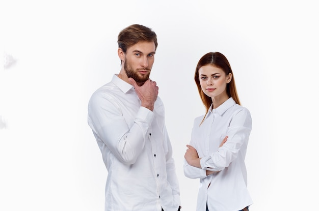 Employees at work a man and a woman in identical shirts on a light background stand opposite each
