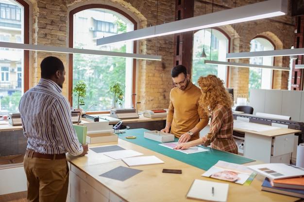 働く従業員。彼の従業員が一緒に一生懸命働いているのを見ているプロジェクトの浅黒い肌のリーダー