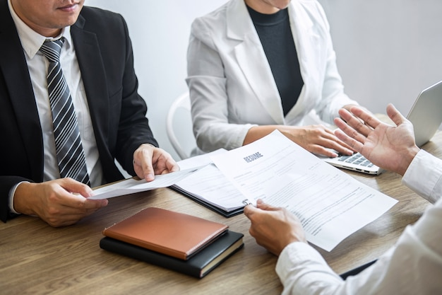 Employer or committee holding reading a resume with talking during about his profile of candidate, employer in suit is conducting a job interview, manager resource employment and recruitment concept
