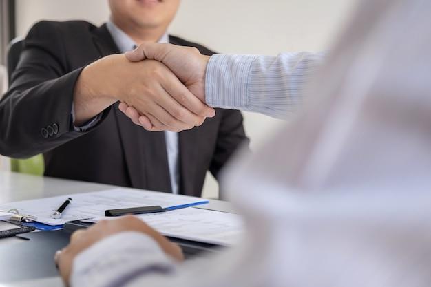 Работодатель в костюме и новый сотрудник пожимают друг другу руки после переговоров и размещения интервью