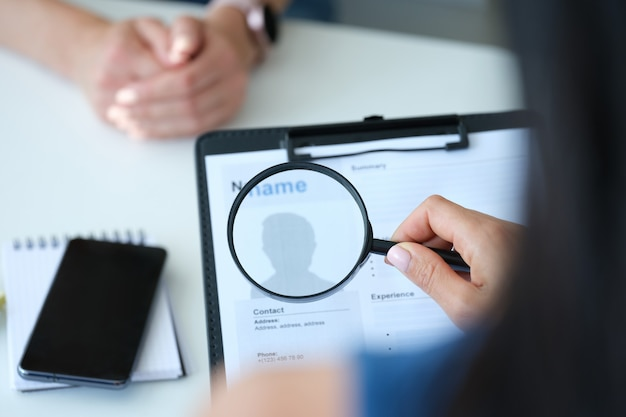Employer looking at application form with magnifying glass closeup