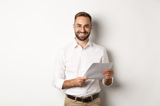 仕事に満足しているように見え、文書を読み、満足している笑顔で立っている雇用主