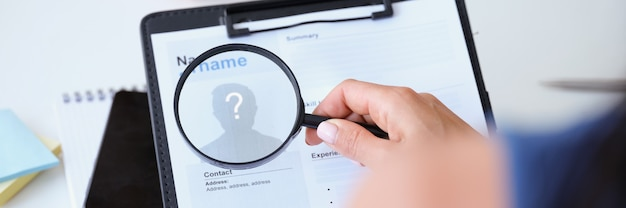 Employer looking at worker resume with magnifying glass closeup