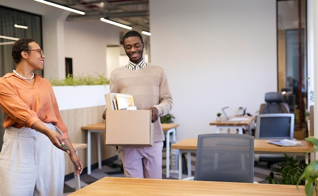 Employer showing man his desk at new job while carrying box of belongings
