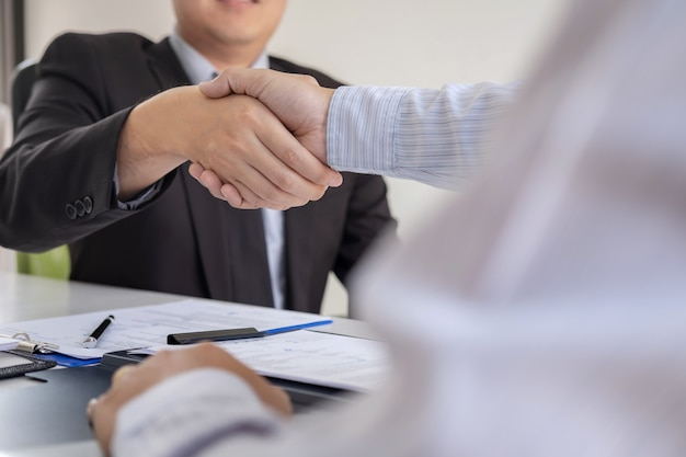 Employer in suit and new employee shaking hands after negotiation and interview placement