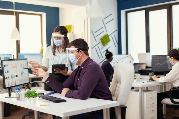 I dipendenti lavorano insieme indossando la maschera facciale come precauzione di sicurezza durante il covid19