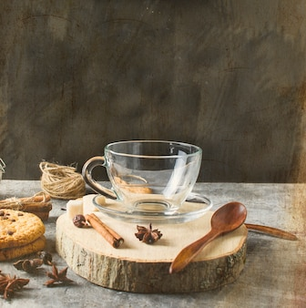 Emply cup for  tea, biscuits, cinnamon, anise on dark   background