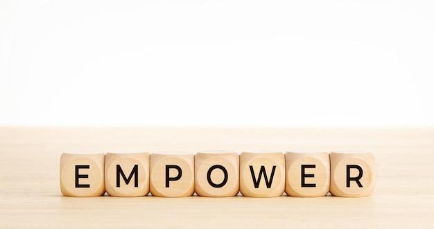 Слово empower на деревянных блоках на деревянном столе. скопируйте пространство.