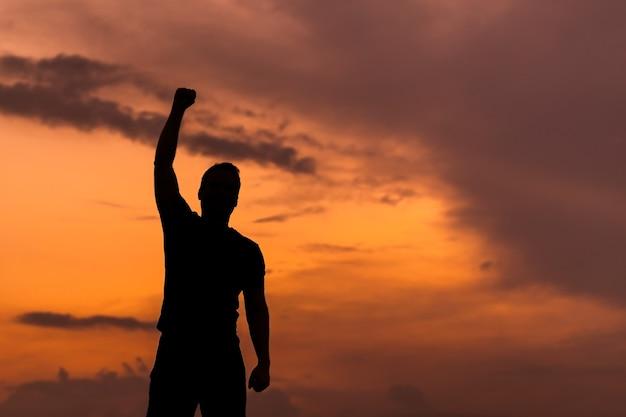 Усиленная концепция с силуэтом сильного мужчины с поднятыми руками на закате