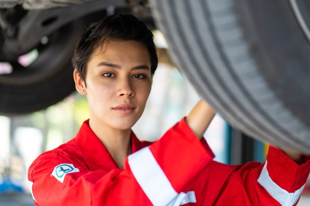Empowering caucasian waman mechanic wearing red uniform working under a vehicle in a car service station