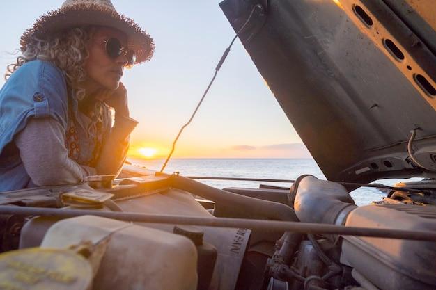 美しい若い大人の女性とのエンパワーメントの概念は、問題を解決するために車のエンジンを見てください-一人で旅行し、人と車との無料の概念-背景に黄金の夕日と海