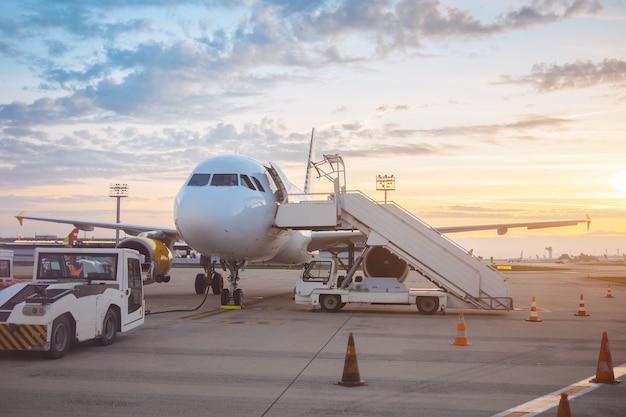 Пассажирский самолет empry на взлетно-посадочной полосе возле терминала в аэропорту во время заката. земля в аэропорту
