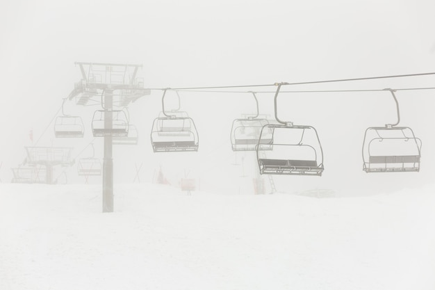 Empty abandoned chairlift during the snowstorm.