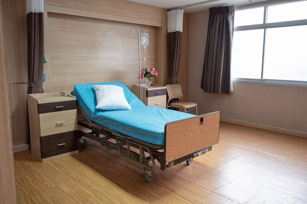 Empty adjustable patient bed with saline solution in private room at hospital ward