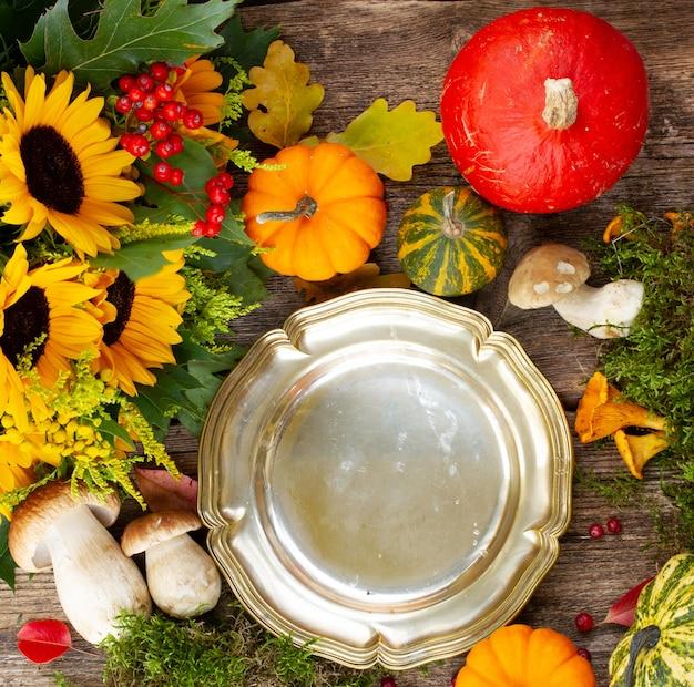 Пустая выдержанная тарелка с грибами, мхом, листьями и рамкой из тыкв на деревянном столе, подготовка к ужину на день благодарения