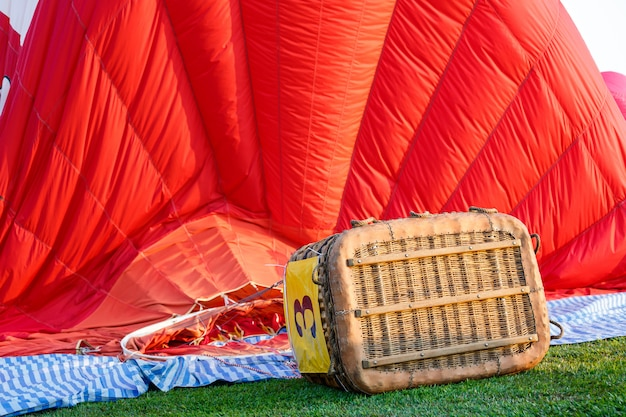 Empty air balloon basket on the ground at evening