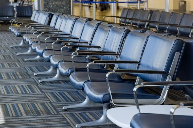 Пустая зона ожидания в зале ожидания вылета аэропорта со стульями