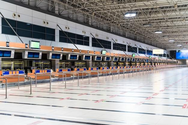 Пустой терминал аэропорта в международном аэропорту во время пандемии коронавируса с отменой ...