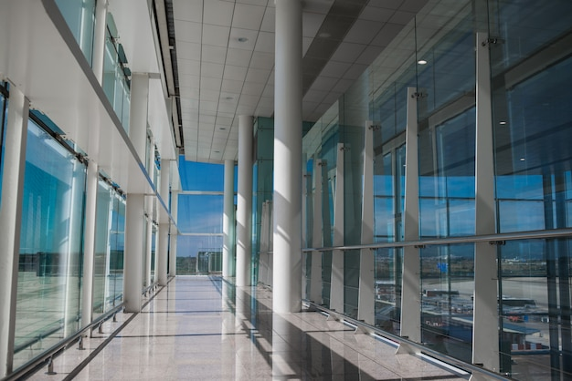 Empty airport hall with glass windows and white column.
