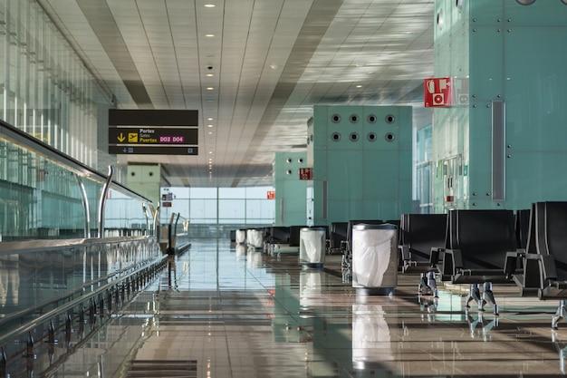 좌석, 무빙 워크웨이, 쓰레기통 및 점수 판이있는 빈 공항 라운지 공간.