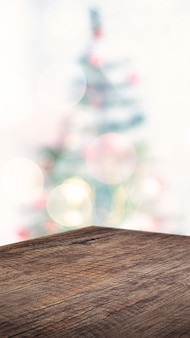 Empty angle brown wood table with abstract christmas tree decor string light blur background