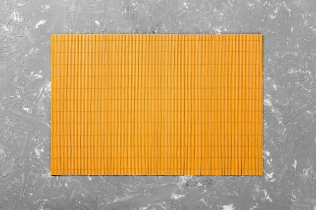 Empty asian food background. yellow bamboo mat on wooden background top view with copyspace flat lay