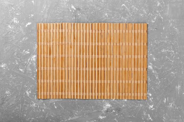 Пустая азиатская еда. коричневая бамбуковая циновка на деревянном фоне вид сверху с плоской планировкой copyspace