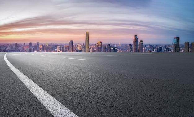 空のアスファルト道路と街のスカイラインと建物の風景、中国。
