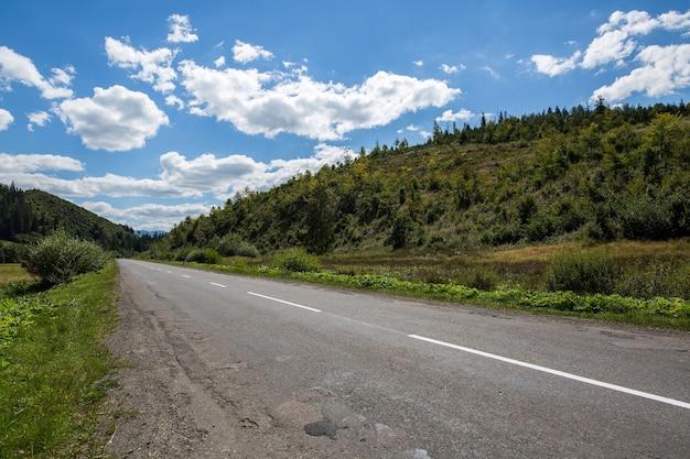 森林に覆われた山々の空のアスファルト道路高速道路、表面は曇り空