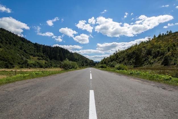 森林に覆われた山々の空のアスファルト道路高速道路
