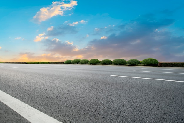 Empty asphalt road and natural landscape in the setting sun