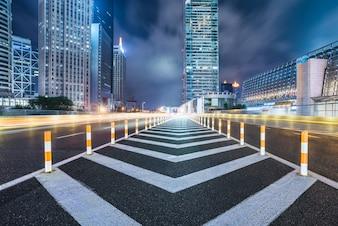 Empty asphalt road through modern city