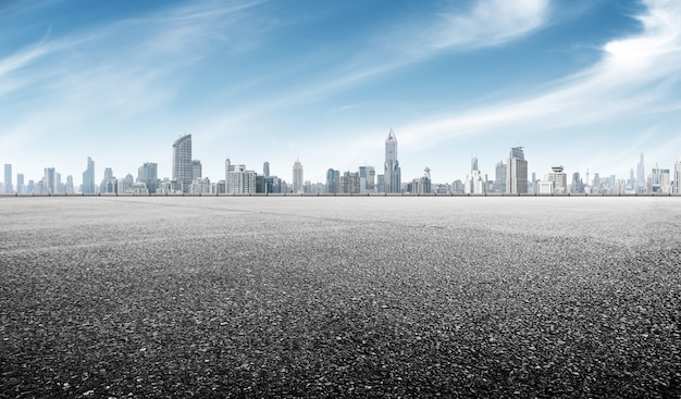 Empty asphalt road with cityscape of shanghai in blue sky