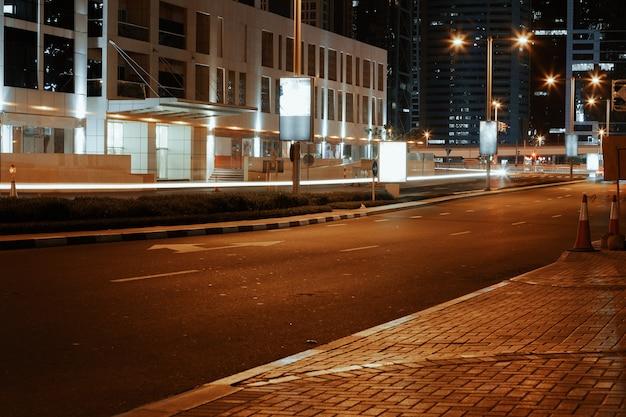 ドバイの夜の近代的な建物と空のアスファルト道路