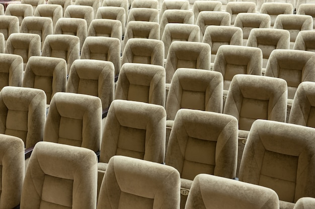 Empty auditorium with beige chairs, theatre hall