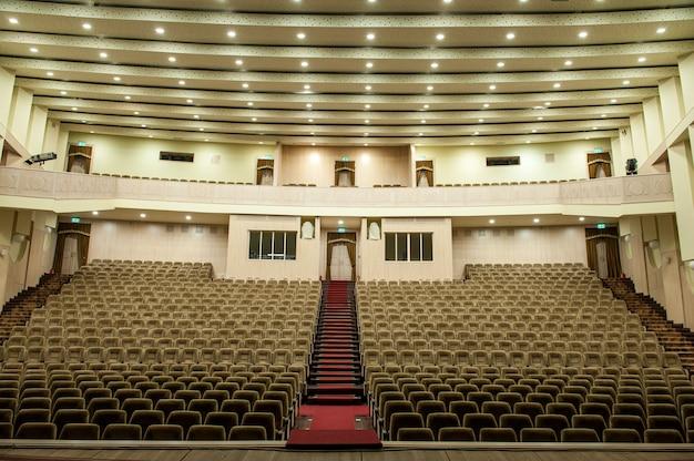ベージュの椅子、劇場、または会議場のある空の講堂。