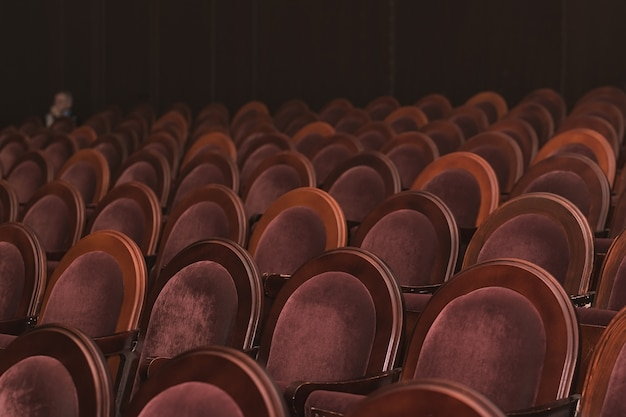 An empty auditorium with a single spectator in the background empty seats in the auditorium