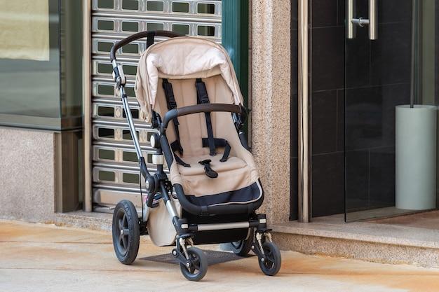 Пустая детская коляска возле открытого входа в магазин