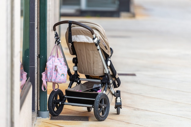 Пустая детская коляска возле магазина на улице