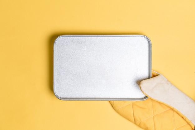 黄色の背景の黄色いオーブン手袋の中に空のベークプレートを置きます。