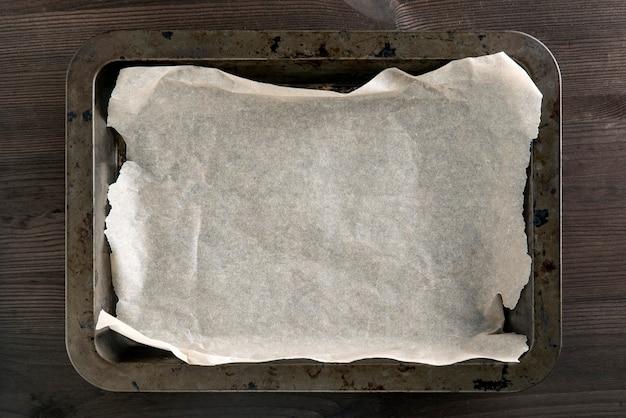 Пустой винтажный противень для выпечки печенья с бумагой для выпечки стоит на темном столе. необходимая посуда. копировать пространство