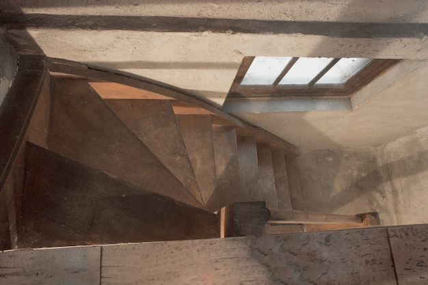 빛이 거의 없고 나무 계단이 어두운 버려진 오래된 산업 건물의 빈 지하실