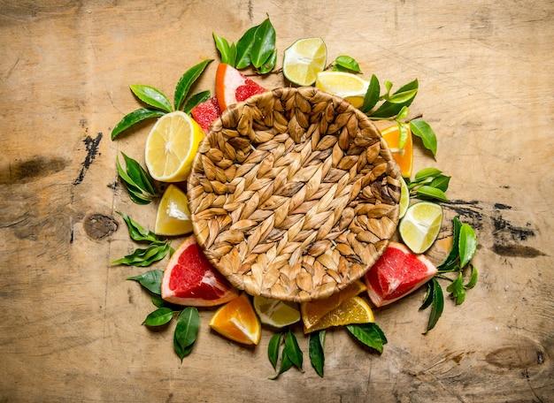 빈 바구니와 자 몽, 오렌지, 귤, 레몬, 라임 나무 테이블에 잎. 평면도