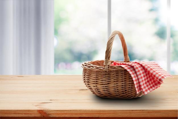 테이블 장소 모형에 빨간 냅킨 피크닉 빈 바구니. 부엌 인테리어와 창문 밖의 여름.